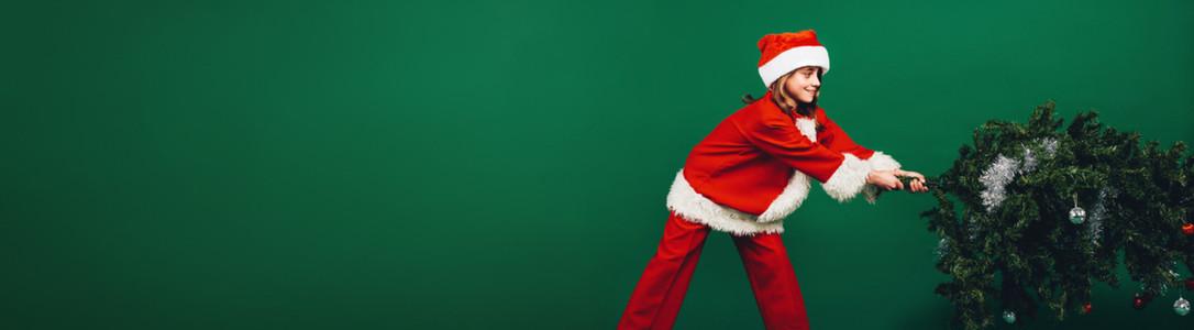 Santa girl setting up a christmas tree