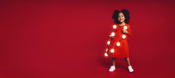Little girl wearing garland of led bulbs