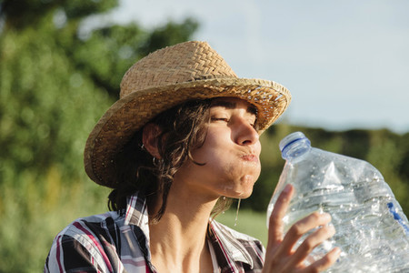 Farmer woman with mouthful of water in a crop field
