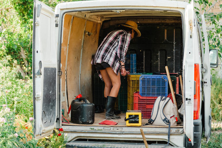 Young farmer woman looking inside a van with hoe