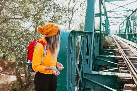 Woman exploring trails and an old iron railroad bridge