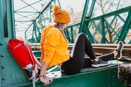 Woman trekking rests on an abandoned old railway bridge