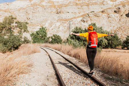 Back view of professional female hiker with tourist backpack exploring wilderness environment during hiking trekking on railway