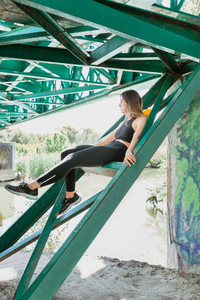 Woman resting between the iron beams of a bridge