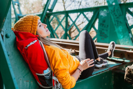Woman trekking rests on an abandoned old railway bridge