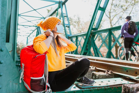 Woman trekking rests on an abandoned railway track with her surgical mask
