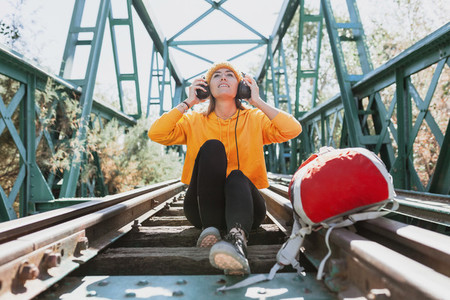 Woman listening to music with her headphones on an abandoned railway bridge