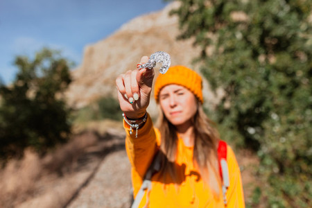 Woman trekking near train tracks picks up trash in nature  Environmental concept