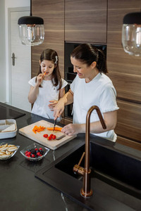 Mother preparing snack for school while her daughter eats carrot
