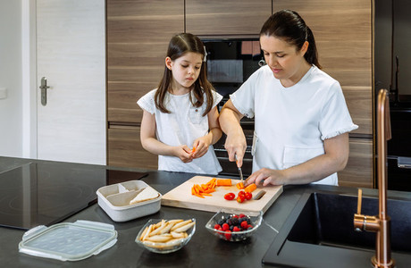 Mother preparing healthy snack for her daughter for school