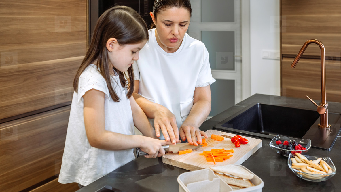 Mother teaching her daughter to cut vegetables for lunch box