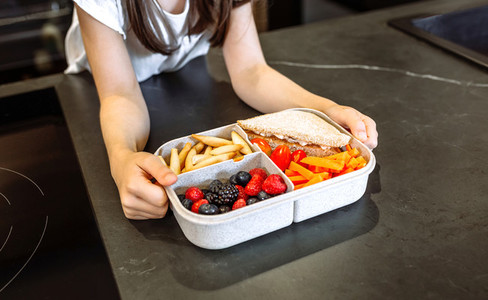 Unrecognizable girl taking lunch box filled with healthy food