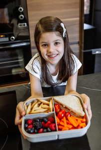 Happy girl showing lunch box filled with healthy food