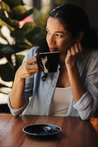 Woman sitting at cafe having coffee