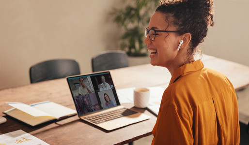 Businesswoman laughing during a video call with team