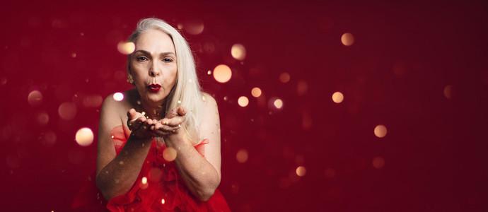 Attractive senior woman blowing glitters