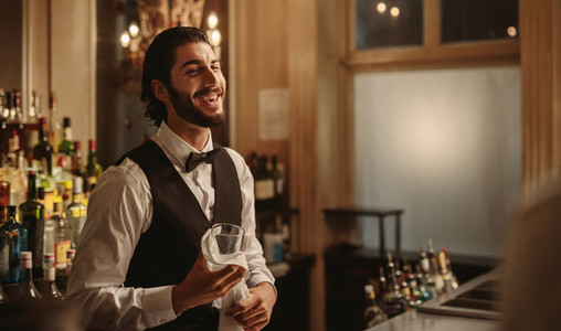 Smiling bartender cleaning glasses