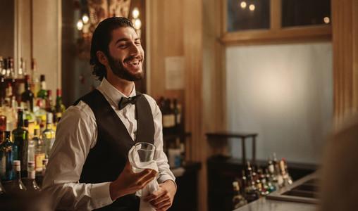 Smiling bartender cleaning glasses