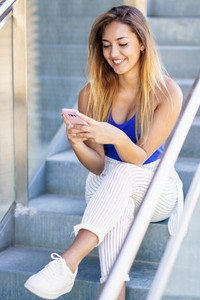 Girl using a touchscreen smartphone wearing casual clothes