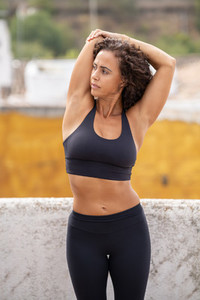 Middle aged woman with fitness body working out on the terrace of her house