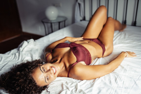Middle aged woman In lingerie posing on the bed