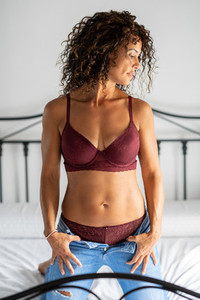 Middle aged woman posing in bra and jeans