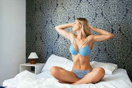 Caucasian blonde woman in blue lingerie stretching her body on the bed