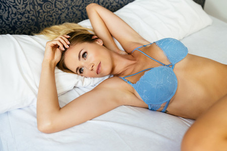 Young woman posing in blue bra and jeans lying on the bed