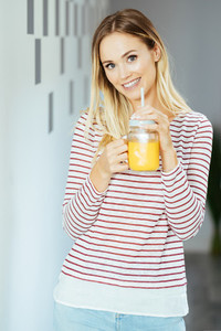 Smiling woman drinking a glass of natural orange juice at home