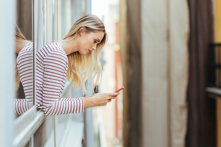 Attractive woman leaning out of her house window using a smartphone