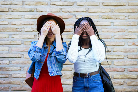 Two female friends covering their eyes outdoors Multiethnic women