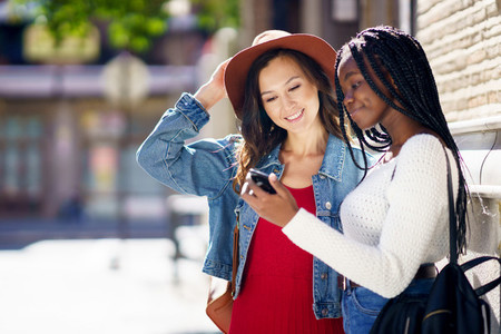 Two friends looking at their smartphone together Multiethnic women