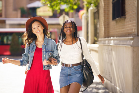 Two female walking together on the street Multiethnic friends