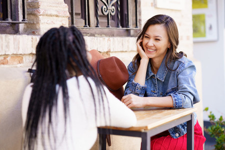 Two multiethnic friends talking sitting at a table outside a bar