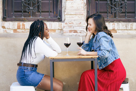 Two multiethnic friends talking sitting at a table outside a bar while drinking a glass of red wine