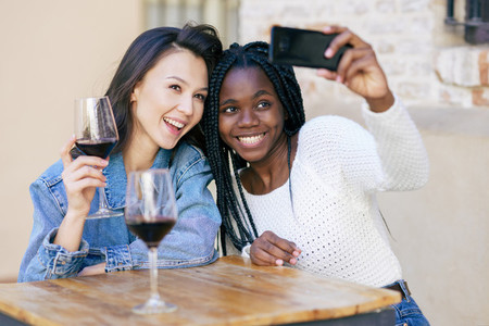 Two friends making a selfie sitting at a table outside a bar while drinking a glass of red wine