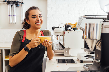 Happy female barista standing