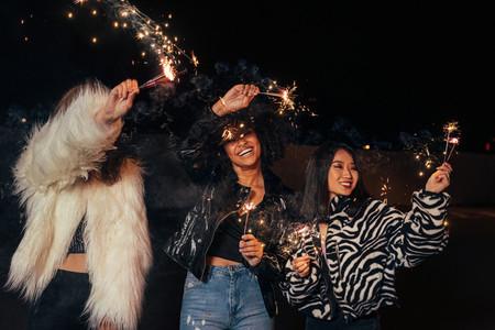 Three happy girls waving