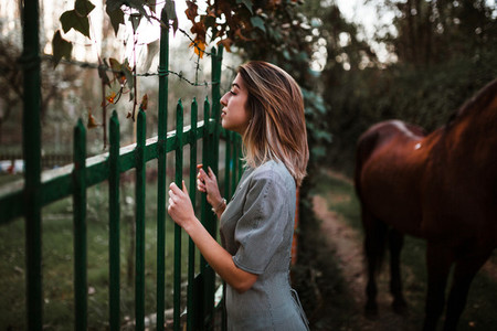 Girl leaning on fence on rural property