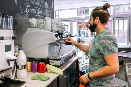 Young waiter preparing the coffee machine
