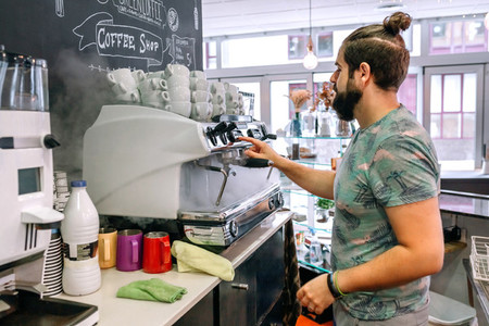 Young waiter preparing the coffee machine
