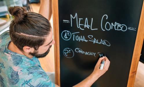 Closeup of young waiter writing the daily menu