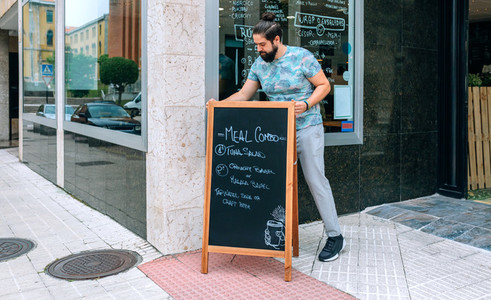 Young waiter placing a blackboard with the daily menu outdoors