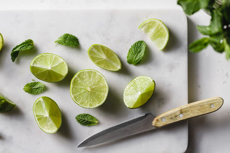 Cutted fresh lime on white marble kitchen board with mint  Preparation beverage or food cooking concept