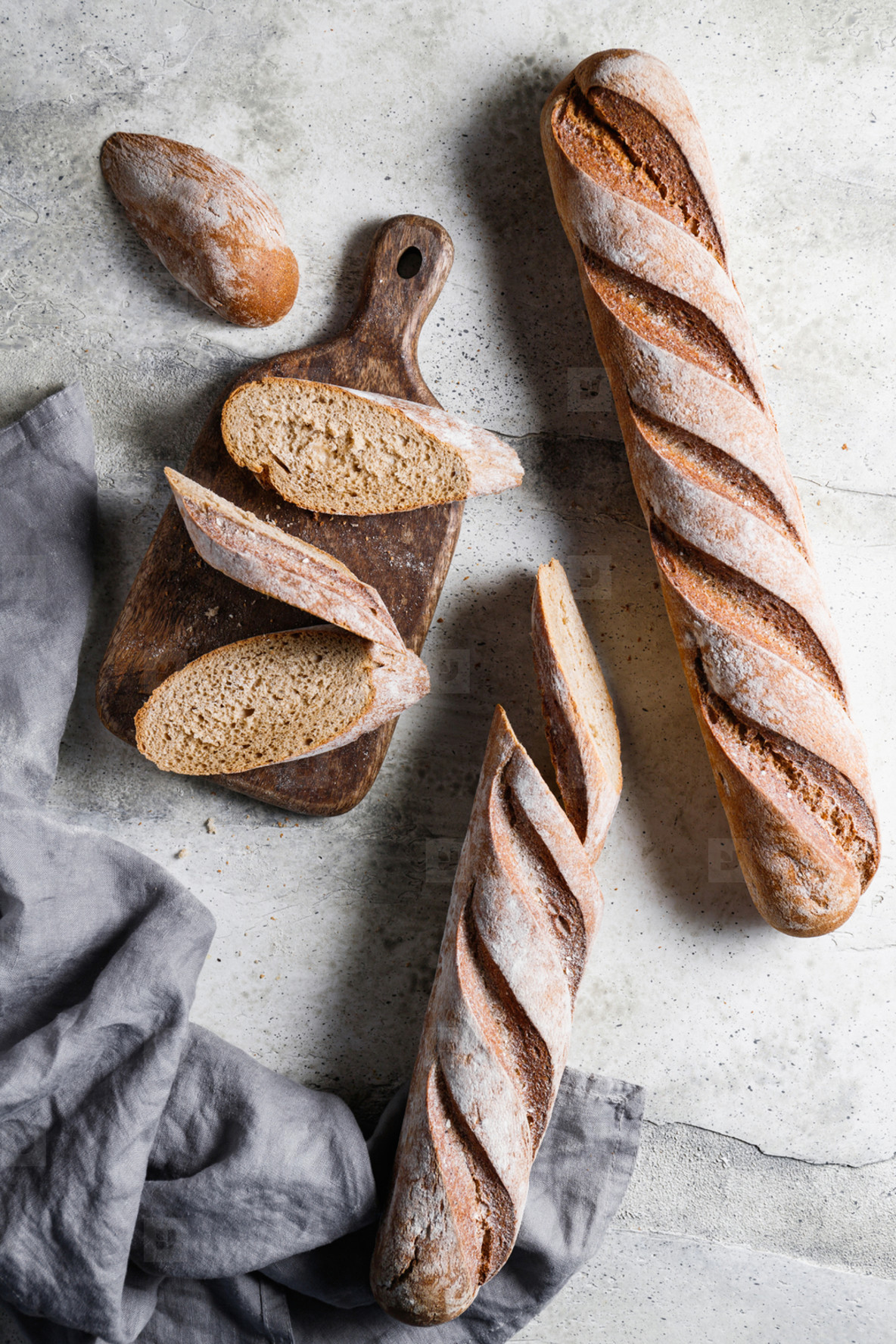 Top view of two brown baguettes on a concrete background