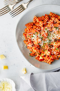 Top view of fusilli pasta with tomato sauce and parmesan cheese