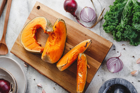 Top view of roasted pumpkin slices on a wooden board  Cooking concept  seasonal fall background