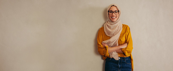 Happy muslim woman standing against a wall