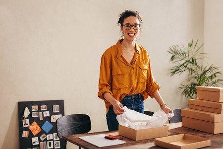 Woman packing parcel boxes for customers at home office