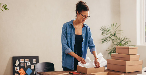 Woman preparing product for deliver to customer